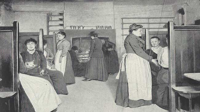 Men and women inside the kitchen of a common lodging house.