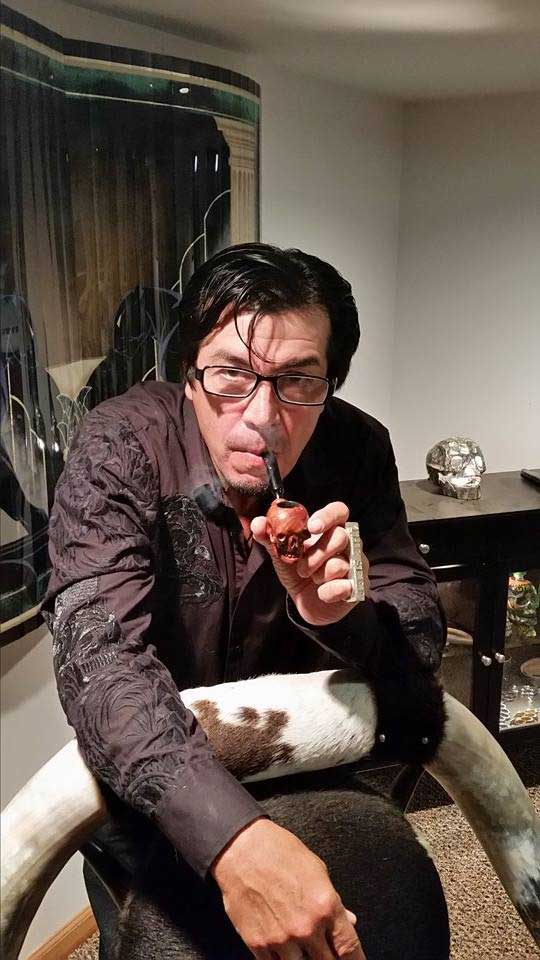 Randy Williams smoking a Sherlock Holmes type pipe.